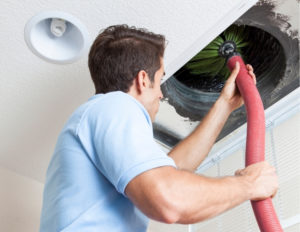 Technician cleaning airduct
